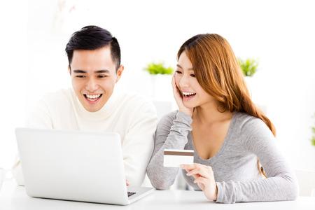 pagando: feliz pareja de jóvenes con tarjeta de crédito y portátil
