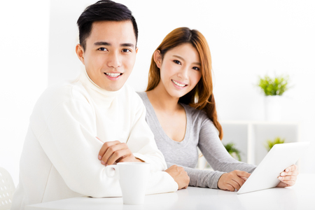 asian boy: happy  Couple Looking at tablet In living room Stock Photo