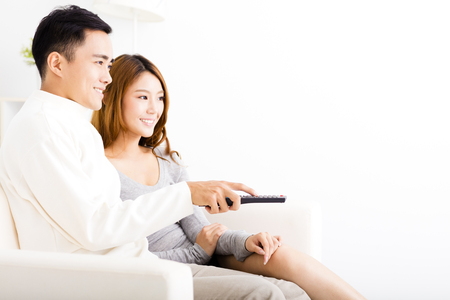 sofa television: happy young couple watching tv in living room Stock Photo