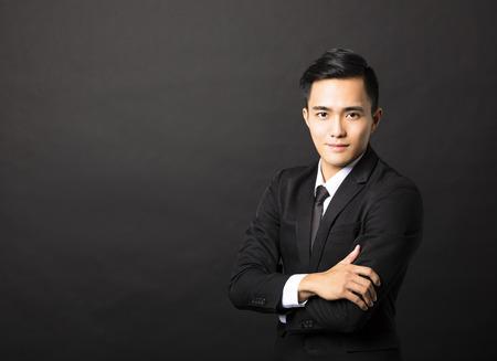 Joven empresario asiático en el fondo negro Foto de archivo - 45900948