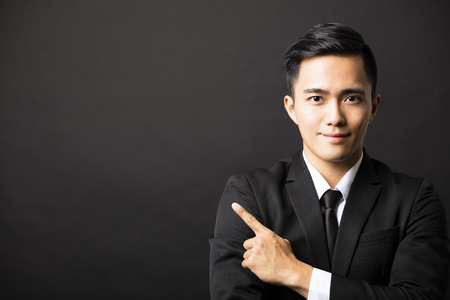 negocio: joven hombre de negocios con gesto señalando