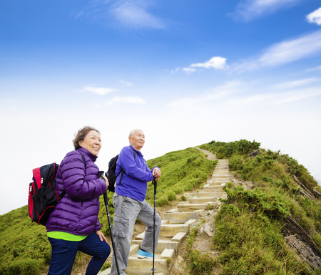 an elderly person: happy asian senior couple hiking on the mountain