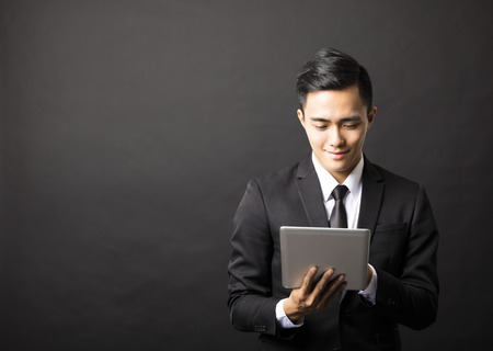 business asia: smiling young business man with tablet pc