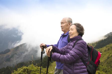 hombres maduros: feliz asiático pareja de ancianos senderismo en la montaña