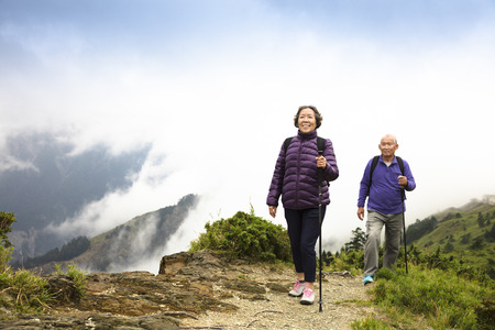 adventure holiday: happy asian senior couple hiking on the mountain