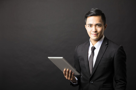 smiling young business man with tablet pc