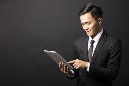 asian business man: smiling young business man with tablet pc