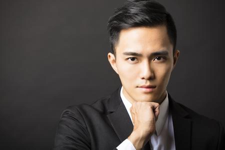 closeup portrait: young asian businessman on black background Stock Photo