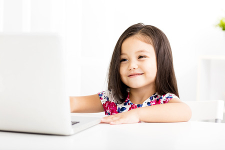 girl studying: Cheerful little girl watching the laptop