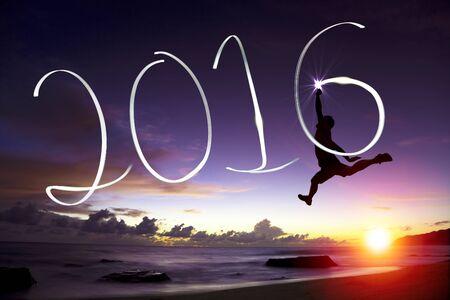 nowy rok: szczęśliwy młody człowiek skoków i rysunek 2016 w powietrzu