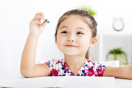 happy little girl writing  in her notebook