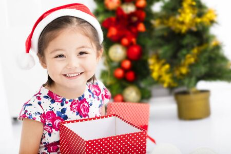 pretty face: happy little girl  in Santa red hat and holding Christmas gift