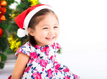 fun background: happy little girl  with Santa  hat in front of  christmas tree Stock Photo