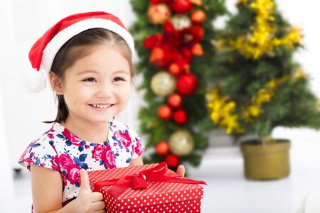 赤いサンタ帽子とクリスマス プレゼントを持って幸せな少女