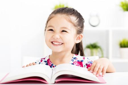 jolie fille: petite fille heureuse lecture d'un livre