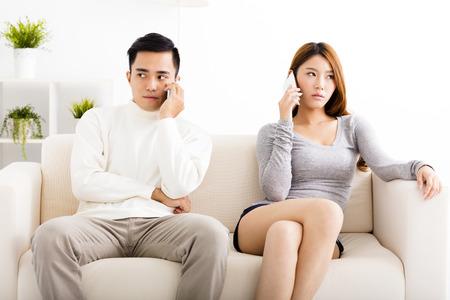 casamento: Jovem casal discutindo sobre os telefones celulares Imagens