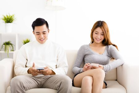 happy young  couple holding mobile phones  on the sofa photo