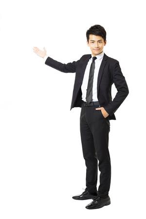 traje: longitud total de joven hombre de negocios que presenta algo