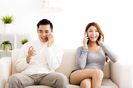 hablando por telefono: feliz pareja joven hablando por los teléfonos