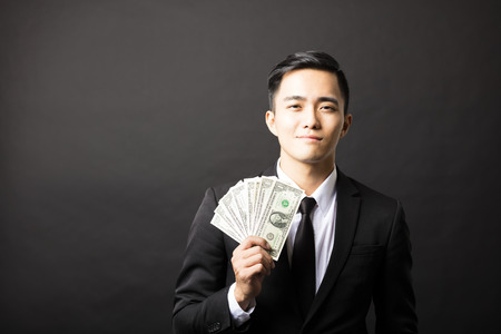young smiling business man holding money Stock Photo