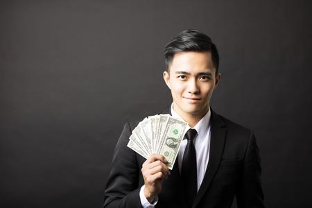 pagando: joven sonriente hombre de negocios la celebración de dinero
