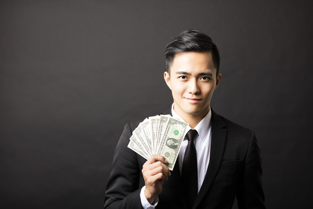 man holding money: young smiling business man holding money Stock Photo