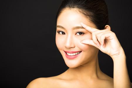 closeup beautiful young woman pointing to eye photo
