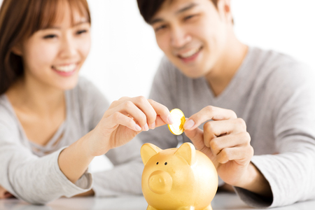 casados: Feliz pareja joven que inserta la moneda en Piggybank Foto de archivo