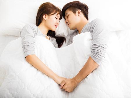 felice giovane bella coppia giace in un letto Archivio Fotografico
