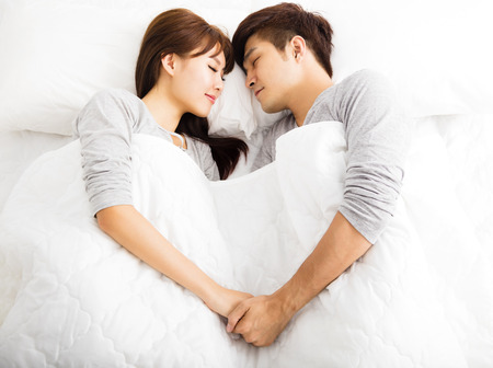 comfortable: happy young lovely couple lying in a bed Stock Photo