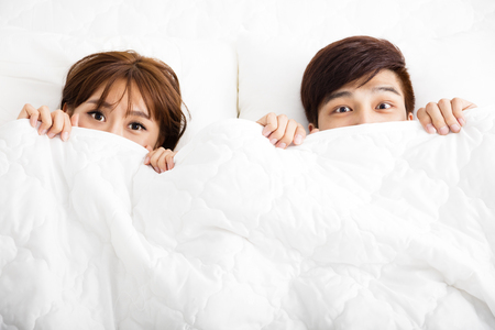 young happy couple: surprised young couple lying in bed Stock Photo