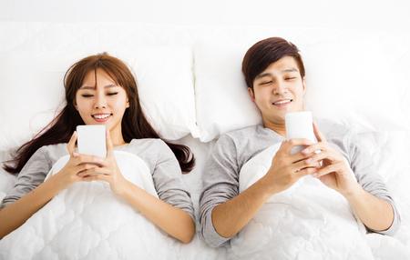 Esposas: joven pareja en la cama con los teléfonos inteligentes