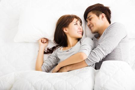 pareja en la cama: feliz pareja encantadora joven tendido en una cama Foto de archivo