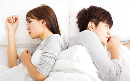 young asian couple: Upset young couple  lying side by side in bed