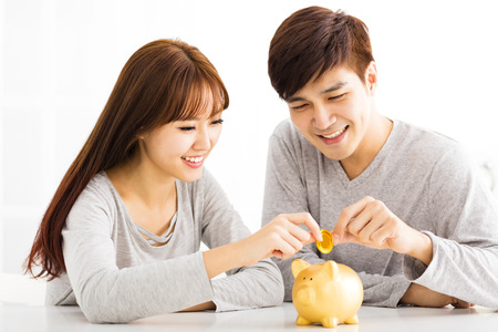 young asian couple: Happy young Couple Inserting Coin In Piggybank