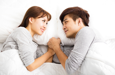 young wife: happy young lovely couple lying in a bed Stock Photo