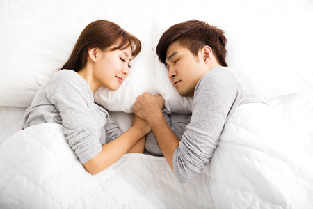 happy young lovely couple lying in a bed 스톡 콘텐츠