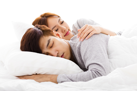 romance bed: happy young lovely couple lying in a bed Stock Photo