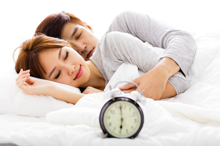 enamorados en la cama: Joven pareja durmiendo en la cama junto a un reloj de alarma Foto de archivo