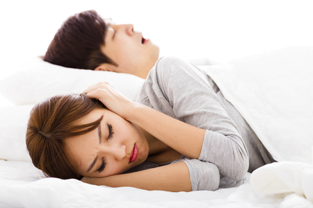 husbands and wives: young Woman covering ears  while  husband is snoring Stock Photo