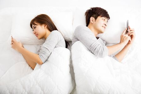 laying on back: happy young couple in a bed with smart phones