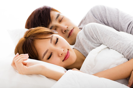 lovely couple: happy young lovely couple lying in a bed Stock Photo
