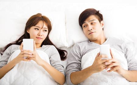 couple au lit: heureux jeune couple dans un lit avec les téléphones intelligents Banque d'images