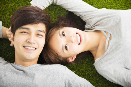 dating: Happy Smiling Couple Relaxing on Green Grass Stock Photo