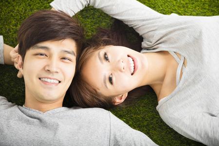 Pares sonrientes felices que se relajan en la hierba verde Foto de archivo