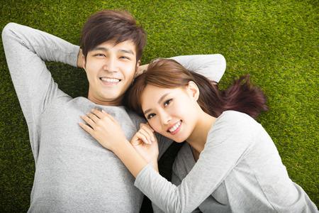esposas: Pares sonrientes felices que se relajan en la hierba verde Foto de archivo