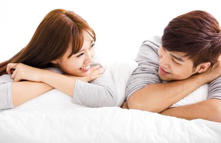 romance: šťastný mladý pár ležící v posteli Reklamní fotografie