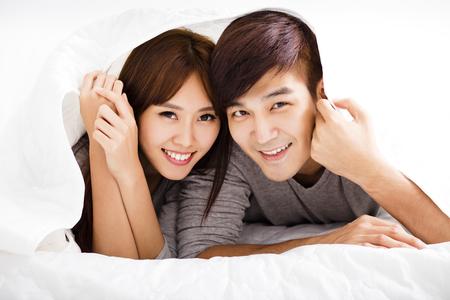 amantes en la cama: feliz pareja joven acostado en una cama