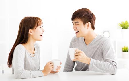 dos personas platicando: joven feliz beber caf� Pareja en sala