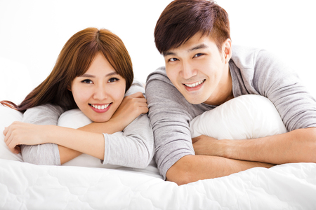 침대에 누워 행복 한 젊은 커플 스톡 콘텐츠